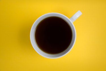 black coffee in white cup on yellow background