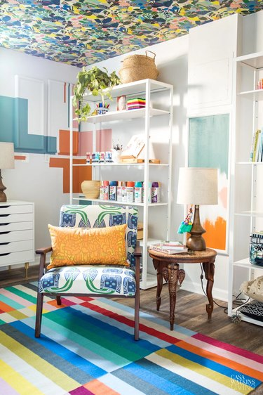 colorful basement office with wallpapered ceiling and chair with orange pillow