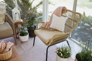 Wicker chair on patio with pink blanket and pillow