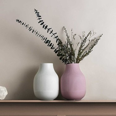 white fluted vase next to pink fluted vase with greenery