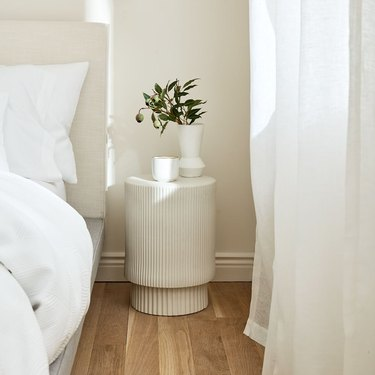 white fluted side table with vases next to bed