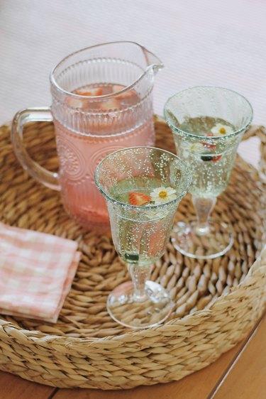 Pink lemonade served inside green plastic goblet glasses for patio