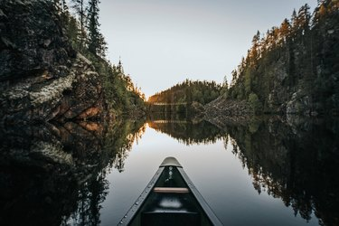 canoe on lake surrounded by forest