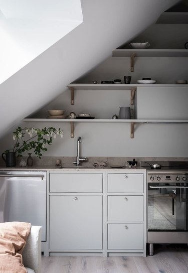 simple and modern kitchen with grey cabinets and open shelving