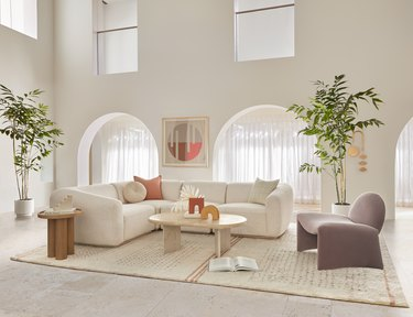 double-height living room with neutral-hued furniture