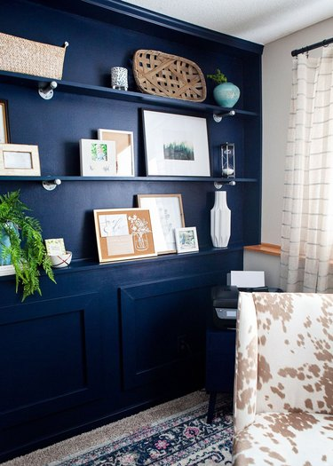 blue monochromatic home office with matching wall shelves