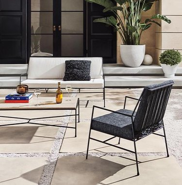 outdoor seating area with chairs and plants in white planters