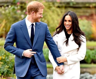meghan markle in white coat with prince harry in blue suit