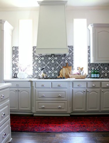 white cathedral cabinets in modern kitchen with black and white patterned backsplash