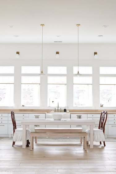 white eat-in kitchen with dining table in kitchen and pendant lights