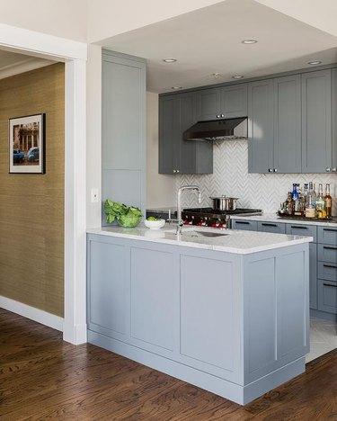 kitchen with light blue cabinets and herringbone backsplash