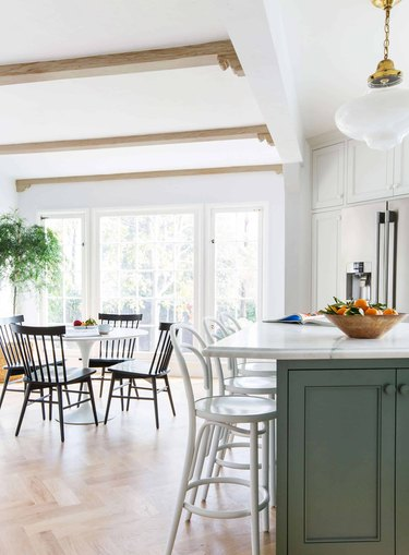 green and white eat-in kitchen with black table and chairs