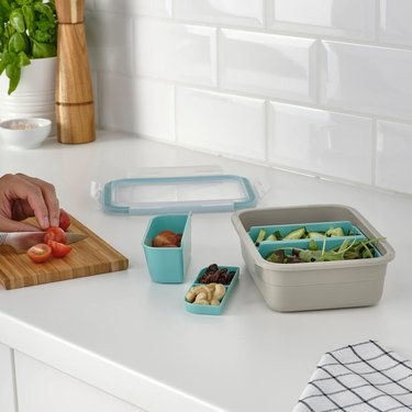lunch box with containers on counter near hand chopping vegetables on a cutting board