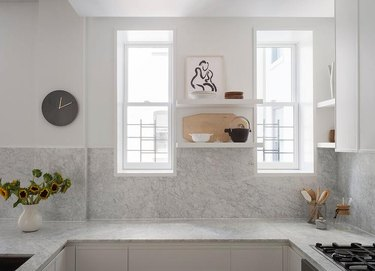 neutral kitchen with marble countertops and backsplash