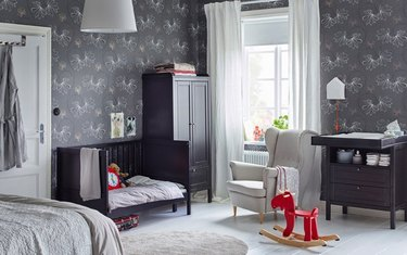 Nursery with gray wallpaper, black crib, changing table, bed, curtains.