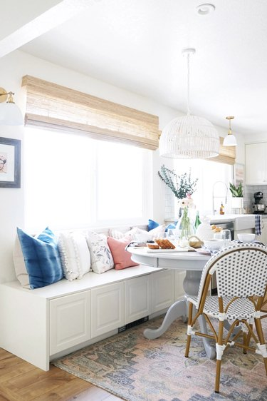 white eat-in kitchen with storage cabinets and bistro chairs