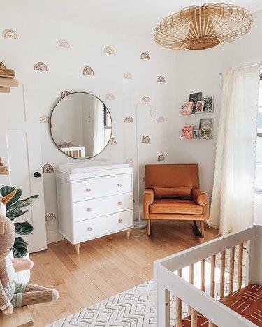 Modern nursery with rainbow pattern wallpaper, white dresser, chair, cane lamp.