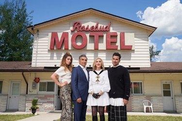the rose family in front of the rosebud motel on schitt's creek