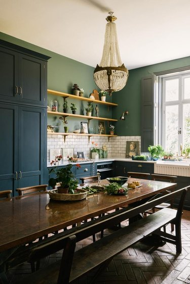 green and white eat-in kitchen with antique chandelier and vintage wood table