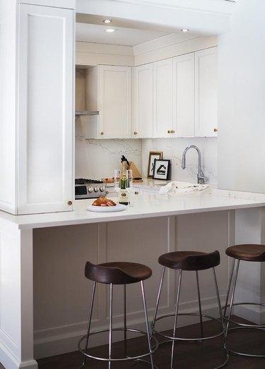 white apartment kitchen with brass hardware