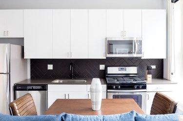 modern kitchen with white cabinets and dark backsplash