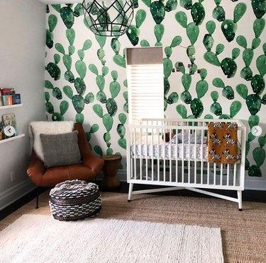 Modern nursery with cactus pattern wallpaper, modern crib, chair, just rugs, poof.