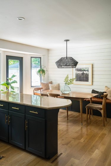 black and white eat-in kitchen with white shiplap wall and breakfast nook