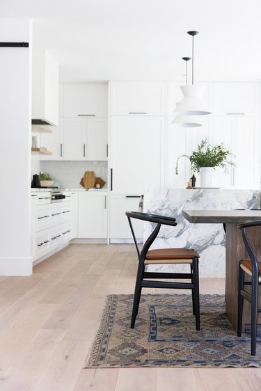 white eat-in kitchen with dining table over vintage area rug