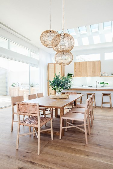 white and wood eat-in kitchen with pendant lights hanging over dining table