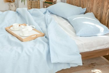 bed with blue linen sheets and tray with tea set