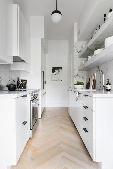 white kitchen with black hardware and marble shelves