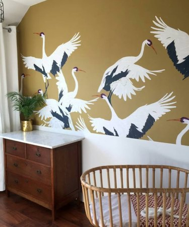Nursery with cane crib, wood dresser, wallpaper with stork pattern.