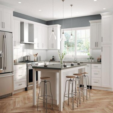 How to Install Crown Molding on Cabinets in white kitchen with wood floor