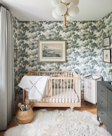 Nursery with leaf pattern wallpaper, light wood crib, sheepskin rug, green dresser.