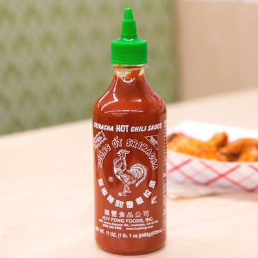 huy fong sriracha chili sauce on wood table with fries