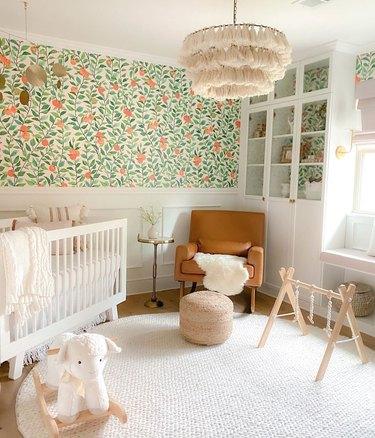 Nursery with citrus pattern wallpaper, tassle lamp, white crib, poof, chair.