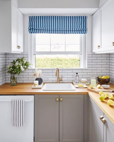 modern kitchen with two-toned cabinets and a striped roman shade