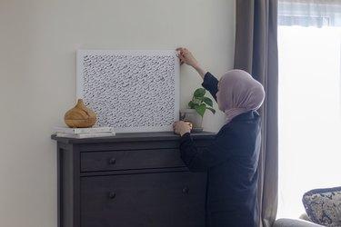 Summar Saad placing an artwork on her wood dresser