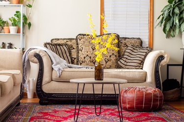 Summar Saad's living room with Persian rug, cream couch, and Moroccan poof and