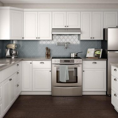 How to Install Crown Molding on Cabinets in kitchen with blue tile backsplash and wood floor