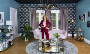 photographer Monica Orozco in red suit with camera in living area