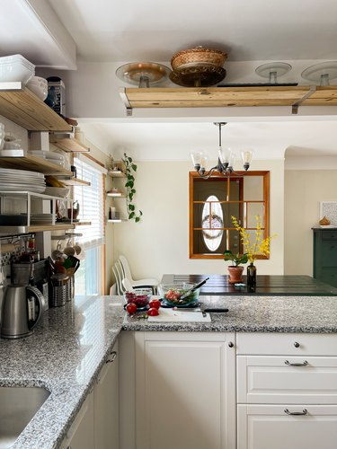 Summar Saad kitchen with white cabinets open shelving and granite countertops