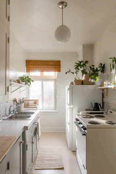 small kitchen with pendant light and two-tone cabinets