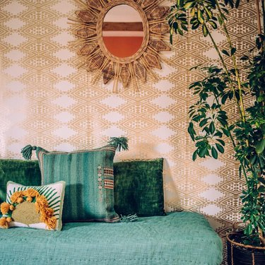 gold patterned wallpaper with green textile accents
