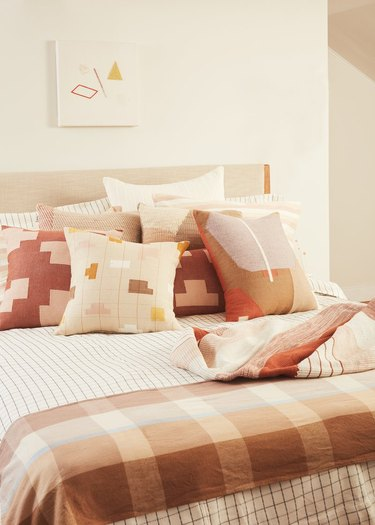pink and neutral textiles on bed