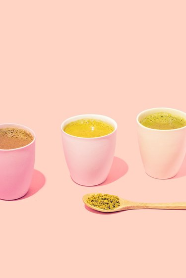 three cups with tea and a spoon with matcha powder