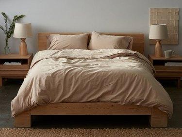 pink neutral bedding on light wood bedframe
