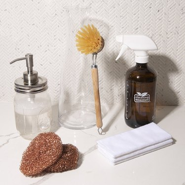 cleaning supplies including a sponge, soap bottle, and and spray bottle
