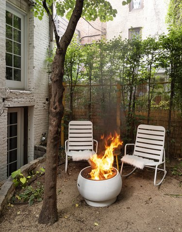 The Novogratz backyard with fire pit and pair of outdoor chairs