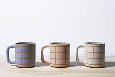 three mugs with grid pattern in various colors